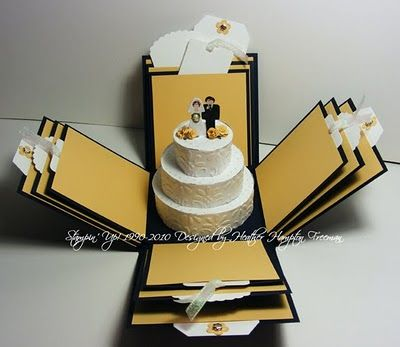 """Explosion Box with wedding cake. Box """"explodes"""" to reveal places to paste pictures or other keepsakes with layered wedding cake in center"""
