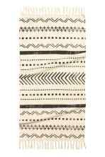 Tapis en coton: Tapis en coton tissé avec motif imprimé. Modèle avec franges sur les largeurs.