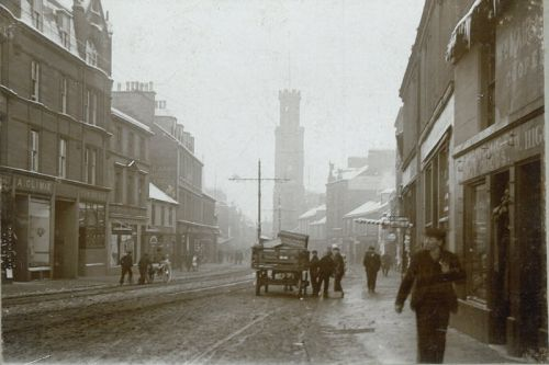 Activity in the High Street south of the Wallace Tower has turned the snow to slush, but icicles still hang from the eaves. To the left can be seen the butcher's shop of Andrew Climie and the Sun Inn Bar, and further along on that side of the street is Matthew Dickie's Ayr Arms Hotel. On the right, the cooperage of William Mair & Son sits above the shop of William Higgins, boot and shoe maker. Although no trams are visible, their tracks and the poles supporting their power cables are in ...