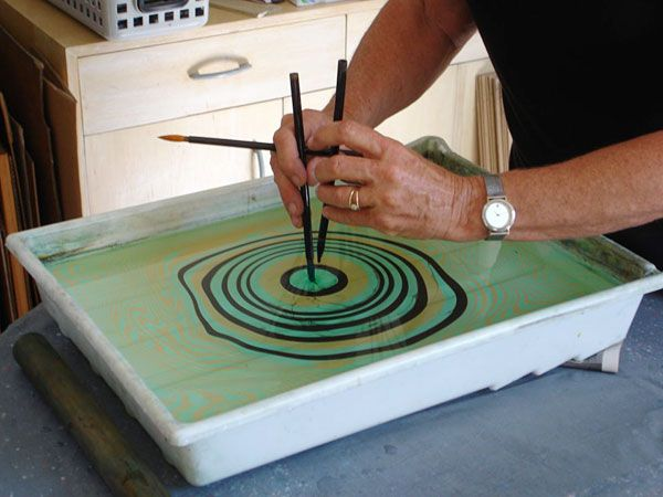 In suminagashi (Japanese paper marbling), the earliest and simplest form of marbling, inks are applied to the surface of the water with tapered brushes. The ink floats and the water urges the spots of colour into concentric bands (as depicted in the image below):