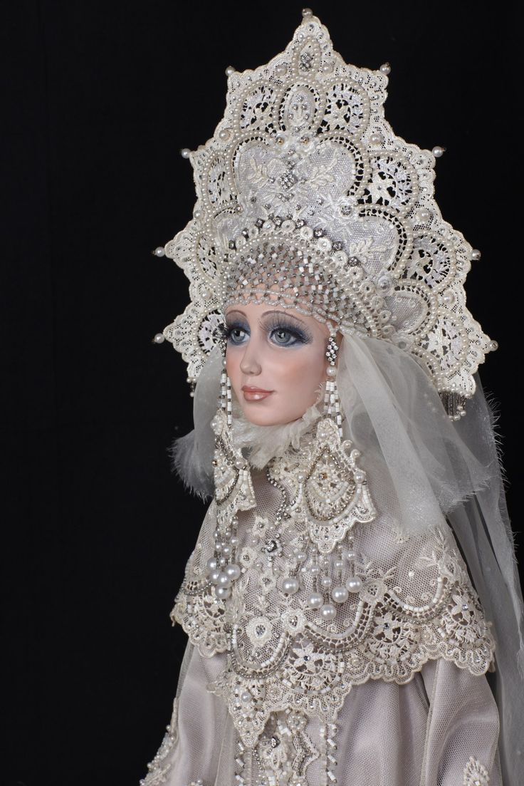 A porcelain doll in a stylized Russian outfit. The outfit and the headdress…