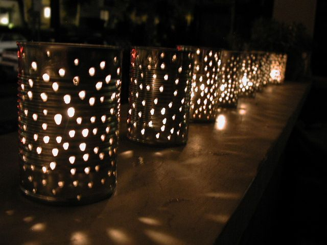 Tin Can Lanterns for table centerpieces. Cheap, recycled, and easy enough to make. Throw a little heat-proof spray paint and ribbons on them to add a little color. Spray gold inside to help it glow brighter.