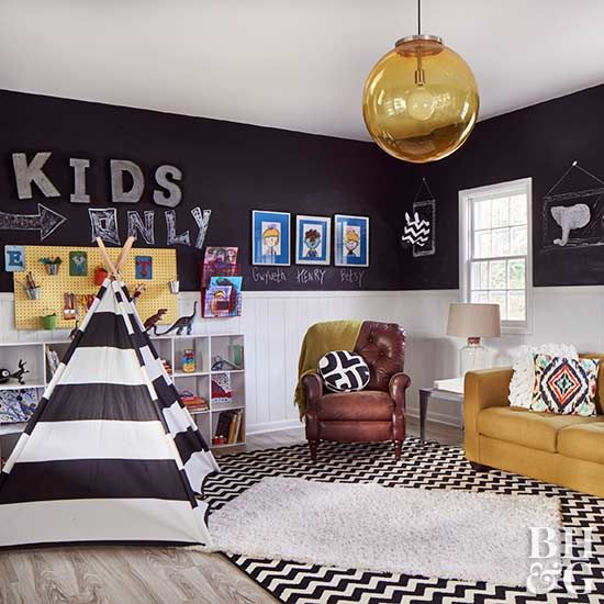 The second-floor bedroom was reimagined as a playroom. The homeowners laid luxury vinyl tile over the existing '60s floor tile, painted the wainscoting white, and gave the kids a huge canvas for artwork, spelling practice, and math problems by dressing the walls with black chalkboard paint. Three-dimensional art hangs on the wall inside chalkboard frames.