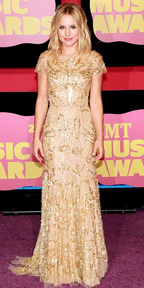 Kristen Bell, the CMT's 2012 host forgoes the outfit Toby Keith recommended – a red bikini top and jean shorts – and instead selects a slightly classier one: a pale-gold, paillette-embellished Reem Acra gown, Graziela earrings, Tresor ring and coral lips.