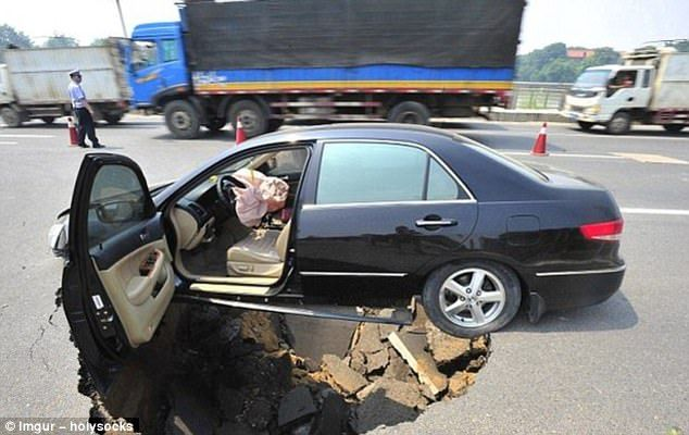 Nearly swallowed: This driver in Jiangxi Province, China, managed to escape without injury after a 13-feet wide sinkhole suddenly appeared in the highway near Nanchang City