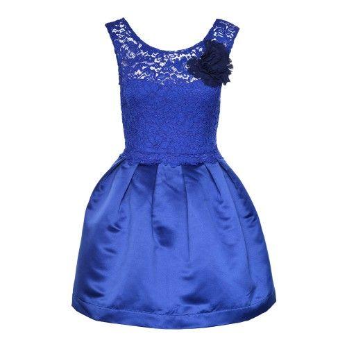 Tweedelige mouwloze jurk met kanten bovenstukje. Rok in een stof met satijnuitzicht, valt gedrapeerd. Bloemenbroche als detail. De pop draagt een S.