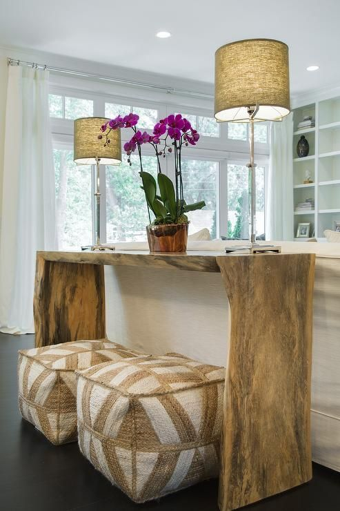 Gorgeous living room features a pair of white and beige poufs tucked under a live edge console table topped with purple orchids.
