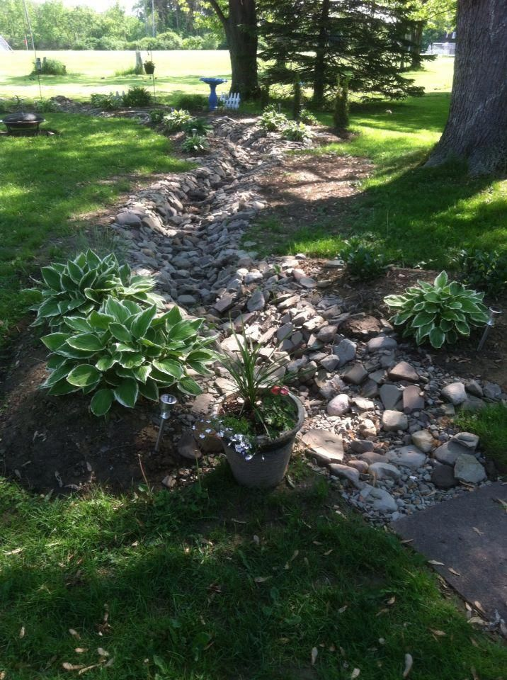 Dry Creek With Drain Tile Has Improved Water Issues On Back Patio Dry Riverbed Landscaping Sloped Garden Landscaping With Rocks