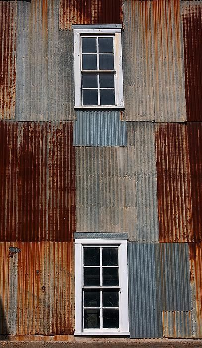 This photograph shows two white windows in a wall made of rusted metal sheeting…