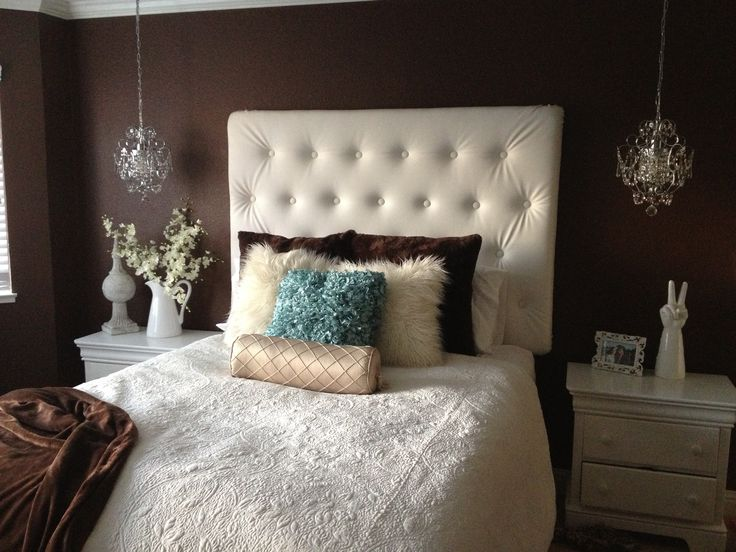 I painted my walls a dark chocolate brown, made my head board out of white pleather, hung chandeliers (I love it more than lamps) , put up crown molding, found a few accents to decorate night stands, topped it off with the pitcher and flowers.  Pop of teal with the pillow! Love my new room:)