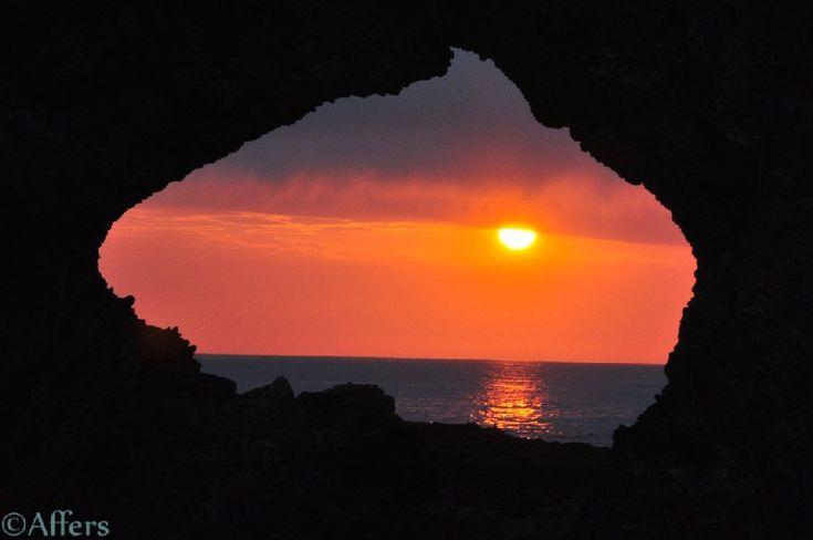 "Sunset looking through ""Australia Rock"" in Narooma, NSW, Australia"