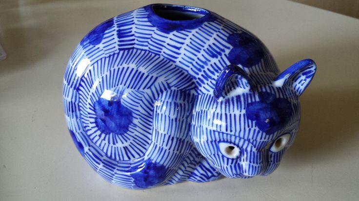Этот уникальный котенок был куплен в Малайзии и, кажется, было сделано, чтобы держать ладан или цветы. Ярко окрашенные синий кобальт штрихов на белом, это коварная штука имеет небольшое отверстие в каждом глазу. Подпись и пронумерованы на дне. Шесть дюймов в длину и четыре с половиной дюймов.