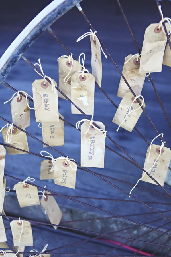 escort cards in bike spokes. would also be neat on a wagon wheel at a country wedding.