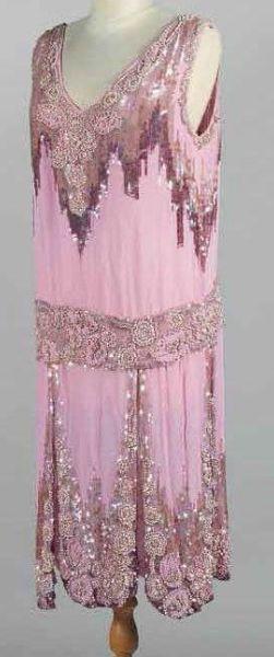 Robe du soir Charleston, anonyme, vers 1925. Crêpe vieux-rose brodée sur le plastron, la ceinture basse et les quilles de motifs floraux en perles dorées et paillettes de gélatine rose et mauve irisées. Ourlet à découpe en pétales.