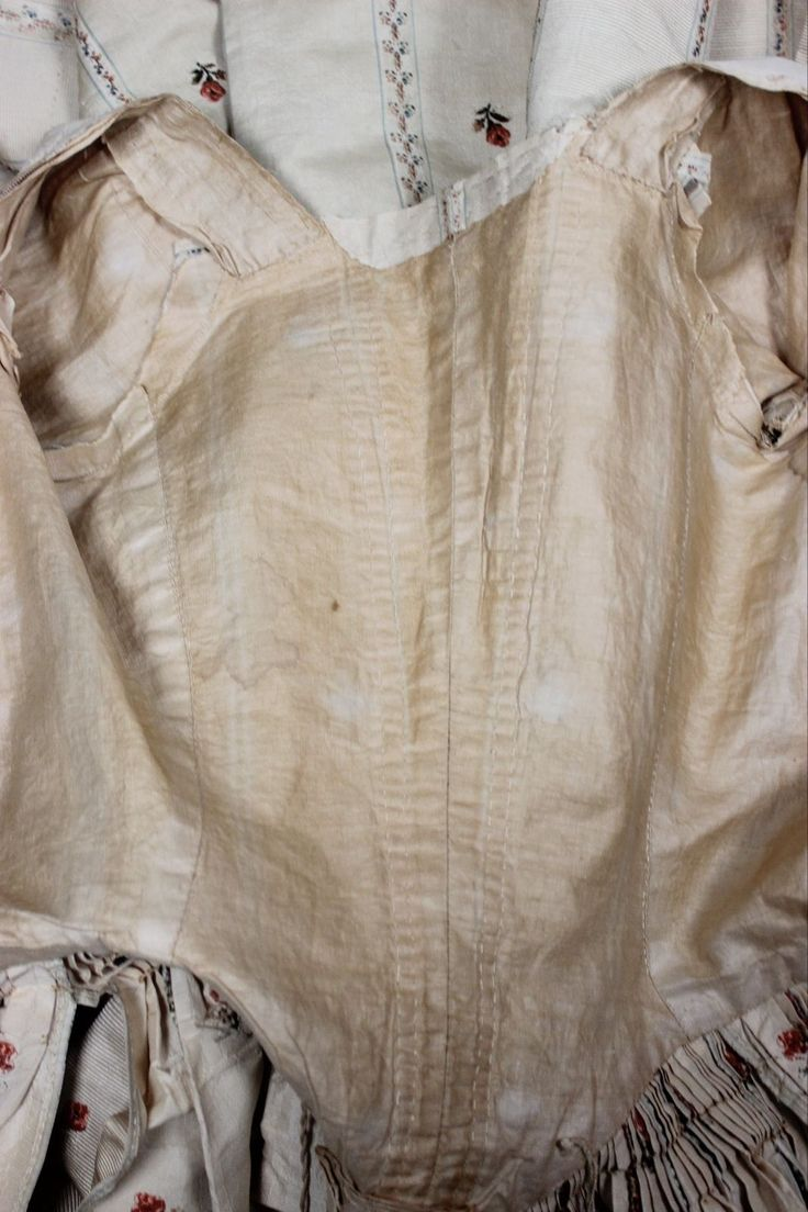 18th Century British Robe in Ivory Ribbed Silk with Polychrome Floral Brocade Posies Stripes Museum deaccessioned from the Metropolitan Museum of Art. This gown is constructed in ivory ribbed silk with polychrome floral brocade posies stripes. It has short sleeves with ruffled cuffs. The back of skirt is constructed with tiny pleats. The bodice is fully lined. There are slits on each side of the skirt for the usage of pockets, these slits are reinforced with hand stitching.