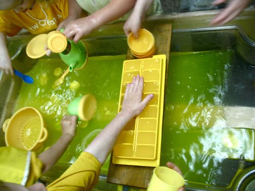 yellow water table adding different elements to water to explore senses
