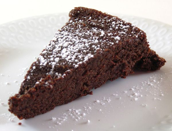 Slice of Easy Flourless Chocolate Cake has just 4 ingredients: butter, bittersweet chocolate, sugar, and eggs.