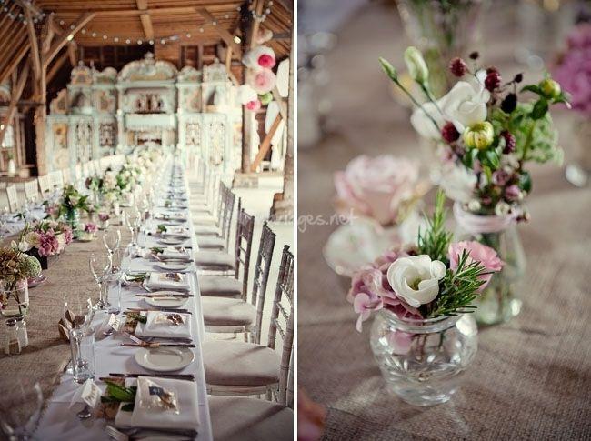 C'est l'idée : nappe blanche, chemin de table en toile de jute et bouquets de couleurs tendres dans des vases en verres (pots de différentes tailles style confiture).
