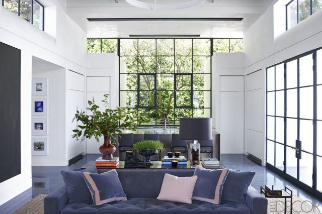 In a sitting area off the kitchen, a sofa from Coup D'Etat is covered in a Holland & Sherry fabric, the table is custom made by Atelier Demiurge, and the 1970s Italian lamp is from Lucca Antiques; the kitchen stools are by Mattaliano.   - ELLEDecor.com