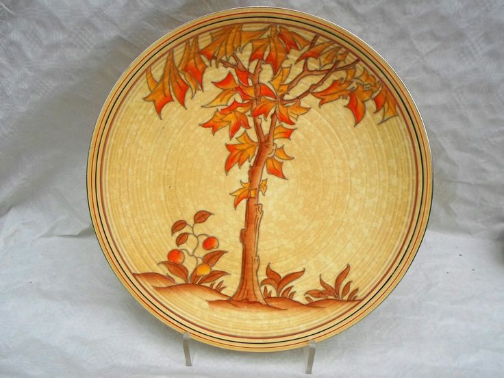 A 1930s Crown Ducal wall plaque, designed by Charlotte Rhead in the 4795 Spanish Tree pattern, having a tube-lined decoration of a stylised tree with leaves in shades of orange and brown, on a buff ground, printed and tubed marks verso to include a Rhead facsimile signature, 36.5cm diameter