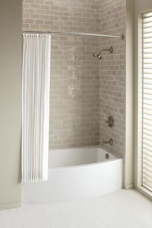 A curved apron bath is about four inches wider in the center of the tub than a standard bath, but then gently curves back to each corner on the exposed wall to fit the space of a standard five foot tub.