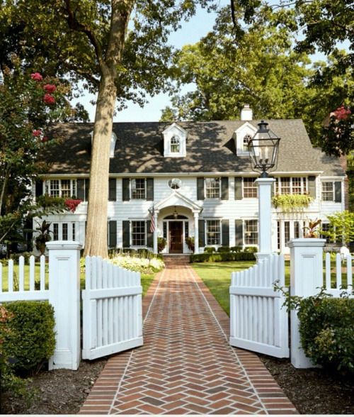 Big double fronted American home with long pathway and white gates