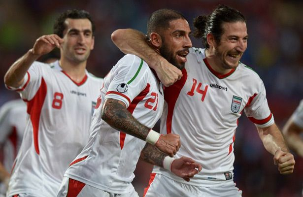 Ashkan Dejagah (#21) celebrates with Andranik Teymourian (#14) after scoring in Iran's 3-0 win over Thailand on Friday. The 2014 World Cup qualifiers need at least a draw in Lebanon on Tuesday to qualify for the 2015 AFC Asian Cup. Photo: AFP.