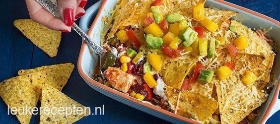 mexicaanse schotel met paprika, mais en kip onder een laagje van tortilla chips en kaas