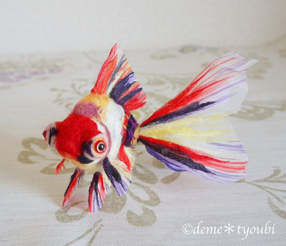 A goldfish made of wool felt.  The Japanese name is Sansyoku Demekin.  It is a…