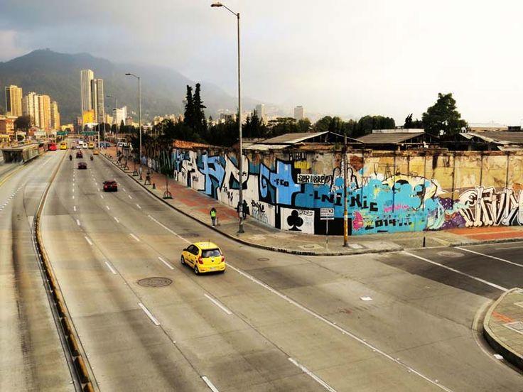 18. Graffiti azul en el muro de toda una esquina de la Calle 26 y al fondo el Centro Internacional y los cerros orientales.