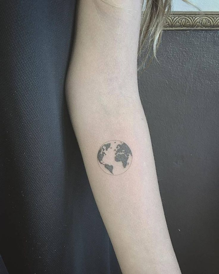 Fine line planet earth tattoo on the left inner forearm.