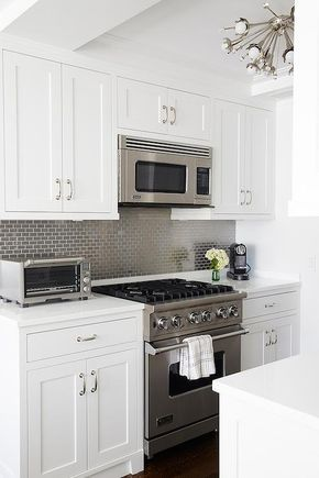 Amazing kitchen features white shaker cabinets paired with white quartz countertops and a stainless steel mini brick tile backsplash.