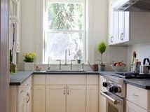 To make a small kitchen seem larger, paint cabinets the same color as the walls.