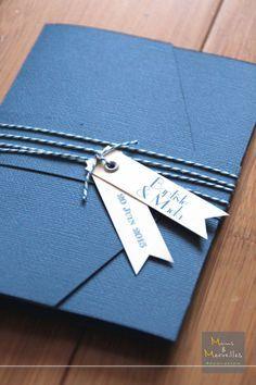 Faire-part pochette pockart bleu marine et ivoire. Ficelle baker twine pour la fermeture, plusieurs volets à l'intérieur et coupon-réponse détachable.