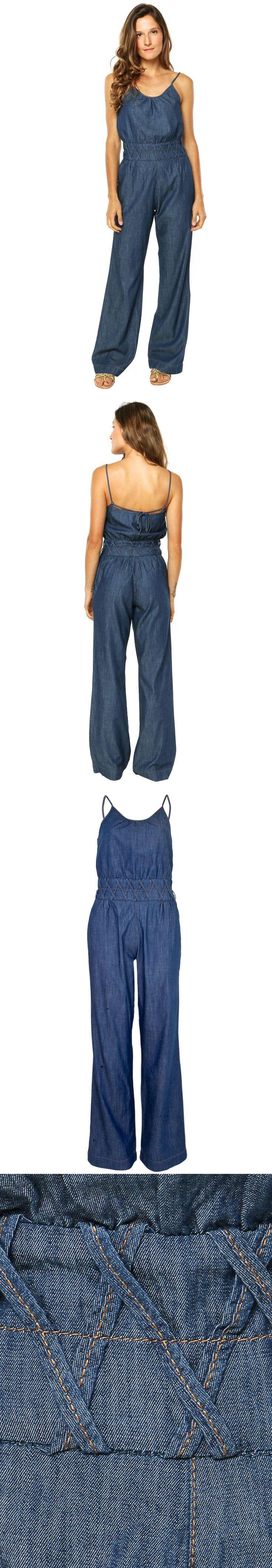 Macacão Jeans Cruzados azul, detalhe de faixas cruzadas na linha da cintura e dois bolsos na parte frontal. Modelagem reta com alças finas e decote arredondado. O Macacão Jeans Cruzados é confeccionado em tecido de toque macio e caimento leve. Fechamento por zíper invisível. Marca: Sacada.
