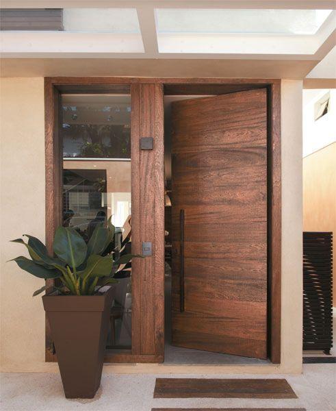 Na entrada, a porta pivotante de angelim-pedra (Unimóveis) ganhou um painel fixo que ilumina a sala.