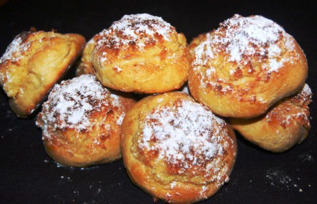 Sweet bread rolls that are round and crispy with powdered sugar and coconut topping.