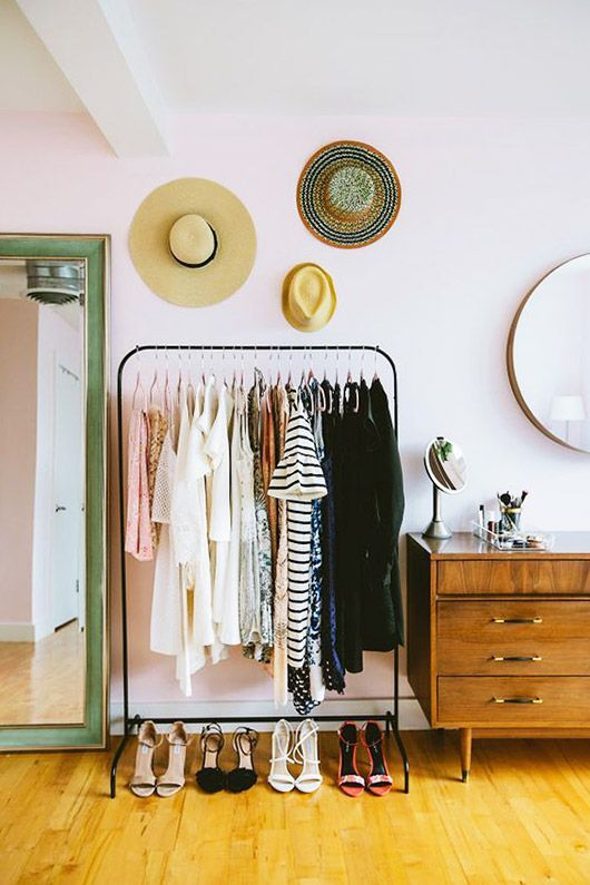 pale pink bedroom with green floor length mirror and black clothing rack with hats hung above and mid-century modern dresser and mirror / sfgirlbybay