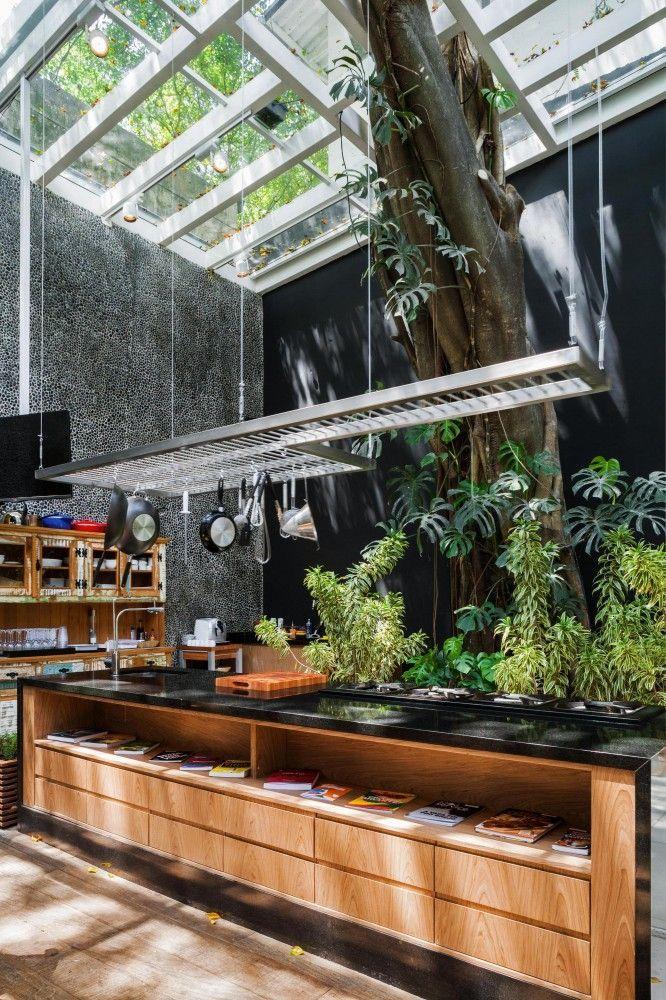 Área para churrasqueira com apoio de acessórios de cozinha suspenso no teto e ampla bancada central