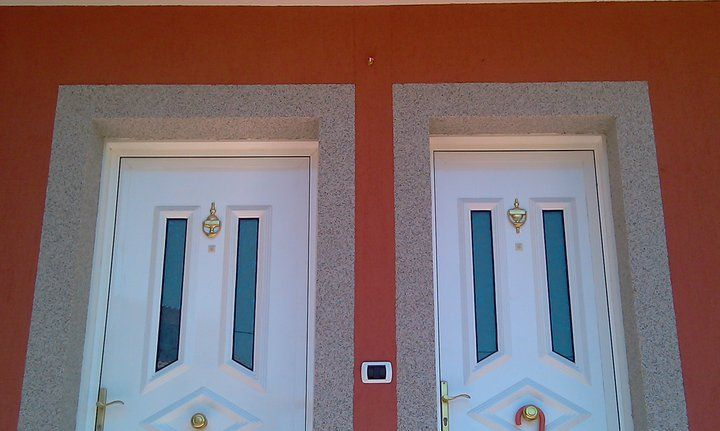 Vivienda rehabilitada en Vigo con sistema SATE Baumit Prosystem. Perfil de arranque de aluminio, placas de EPS de 60mm. tacos de anclaje, malla de fibra de vidrio embebida en mortero especial hidrófugo, imprimación y acabado con revoque de resina de silicona. Obra totalmente acabada. Detalle de recercados acabados con imitación piedra en puertas de entrada a vivienda.