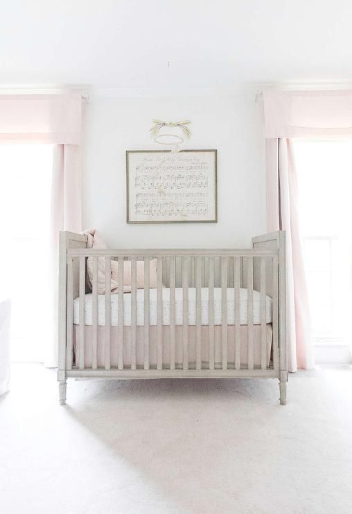 A Restoration Hardware Baby & Child Marcelle Crib is positioned on a RH Baby & Child Scallop Wool Rug beneath a framed Antique Sheet Music - Hush Little Baby mounted between windows dressed in Cotton Canvas Drapery Panels.