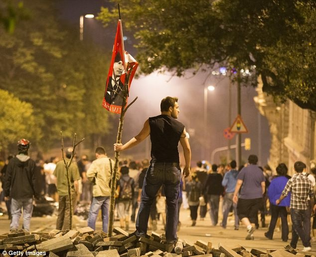 A man holds a flag bearing the image of Mustafa Kemal Ataturk, who founded modern, secular Turkey on the ashes of the Ottoman Empire in 1923 and encouraged the country to throw off its religious traditions