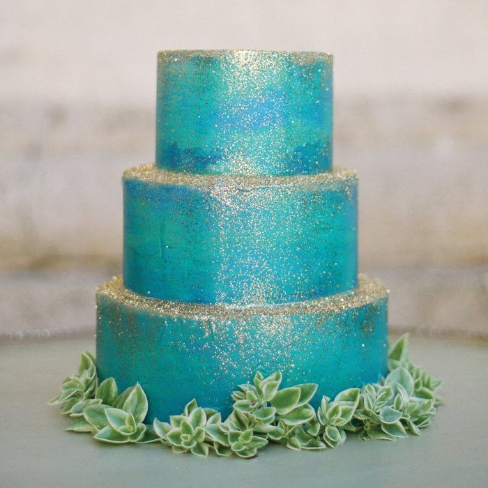 A watercolor-inspired cake topped with glitter is the perfect fit for a glamorous beach wedding.