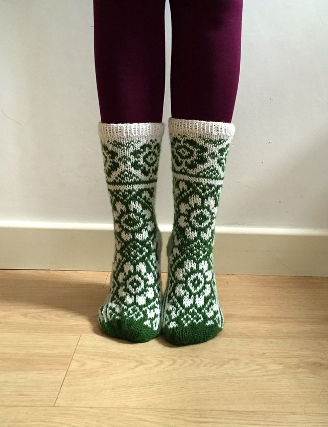 hand-knitted wool socks featuring a white and green floral pattern with a Scandinavian / Fair Isle feel