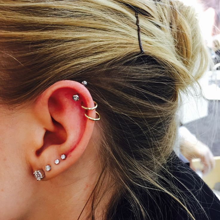 Beautiful ear adorned with four lobe and three helix piercings, the top one freshly pierced with the gentle Studex System 75