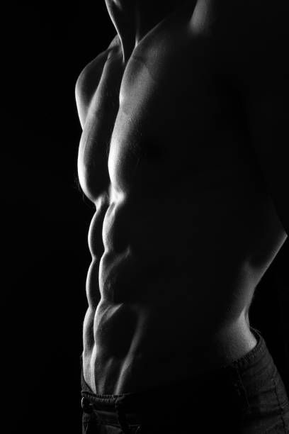 muscular torso of sexy shirtless young male model close up on black