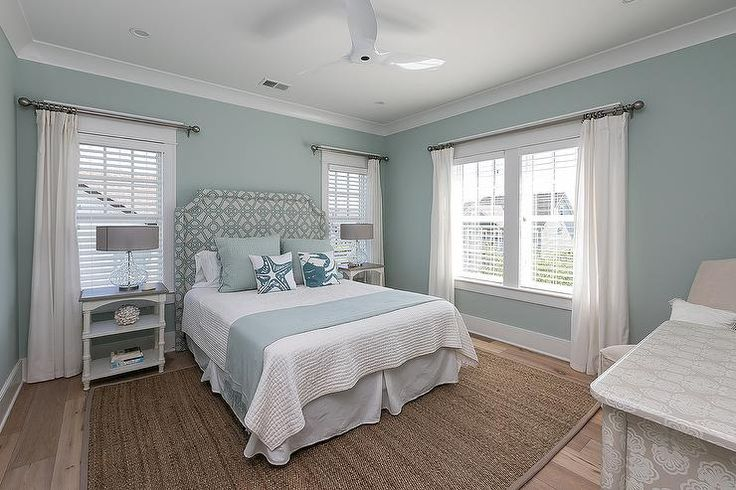 Relax in this beautifully appointed blue and white cottage bedroom featuring windows dressed in white curtains fixed above stained wood top white nightstands illuminated by glass lamps flanking a blue trellis headboard supporting a bed dressed in white bedding topped with a pale blue throw blanket and blue pillows layered behind blue and white accent pillows.