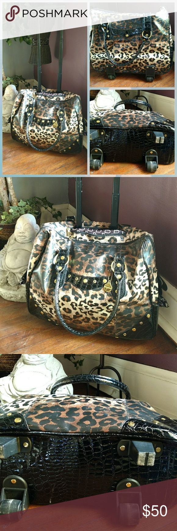 Big Buddha Rolling Leopard Print Bag I've used this a few times. It shows a little wear on the wheels as pictured otherwise it's in very good condition. Big Buddha Bags Travel Bags