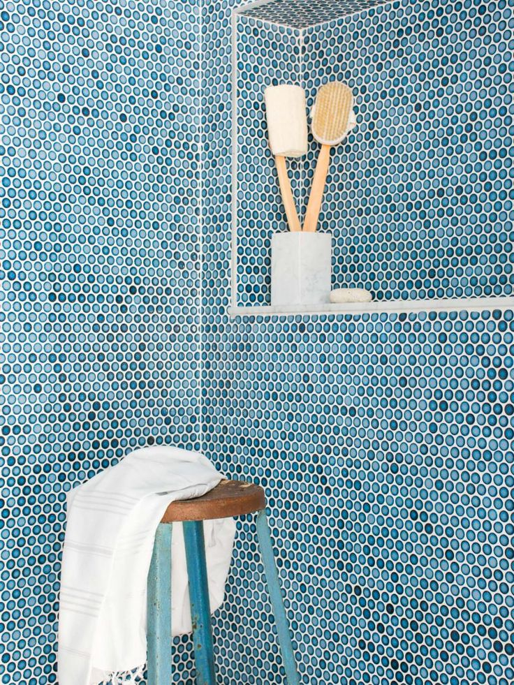 Brilliant blue penny tile walls bring a coastal touch into the bathroom, while a sleek white vanity and eye-catching artwork add interest.