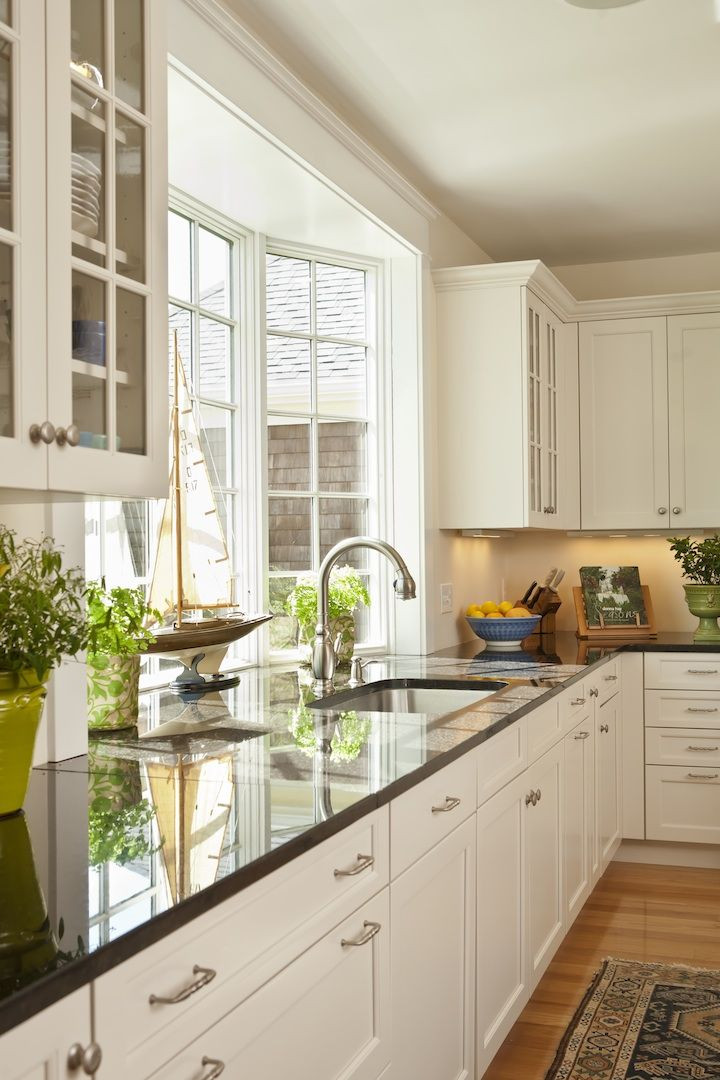 White cabinets with brushed/satin nickel finishes - low kitchen window over sink.  Like the white cabinets with brushed nickel hardware. Granite a bit too dark for what I'm thinking given I want dark floors (SouthernHome.com)
